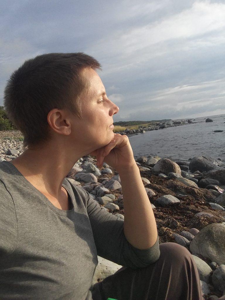 Jenny sitter på en stenstrand och tittar ut över havet