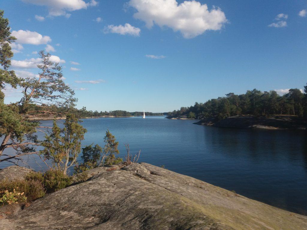 Klippa, skärgårdsmiljö, segelbåt långt borta. Också bra miljö för att lyssna på sommar i P1.