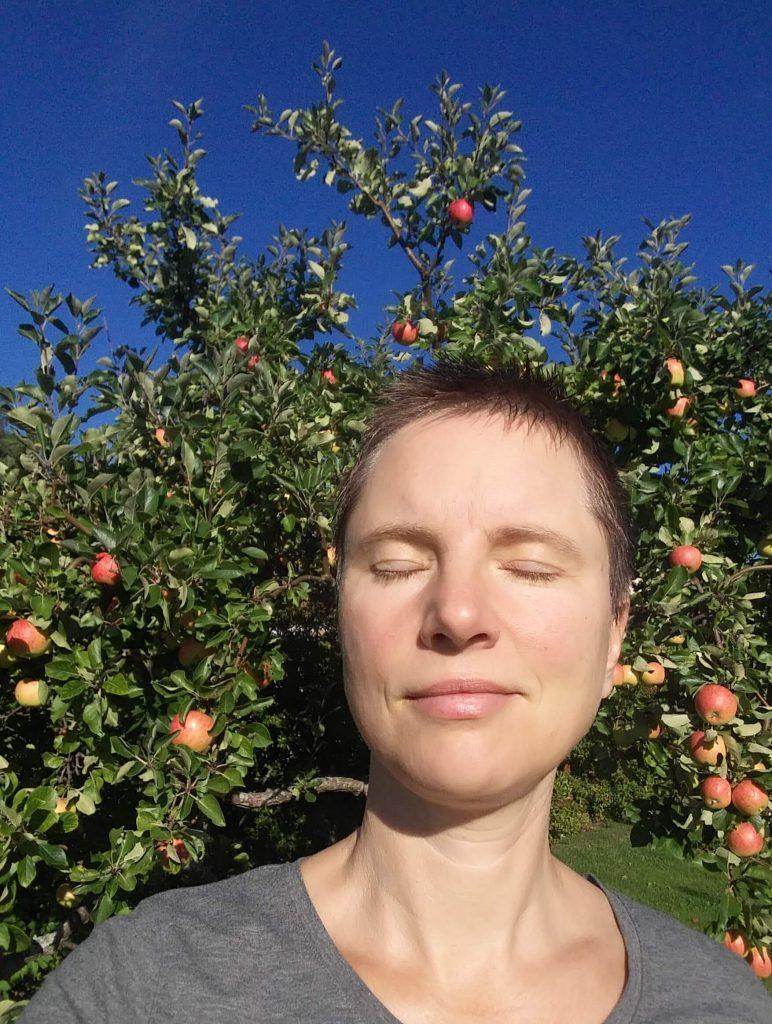 Jenny njuter av solen framför ett äppelträd i september