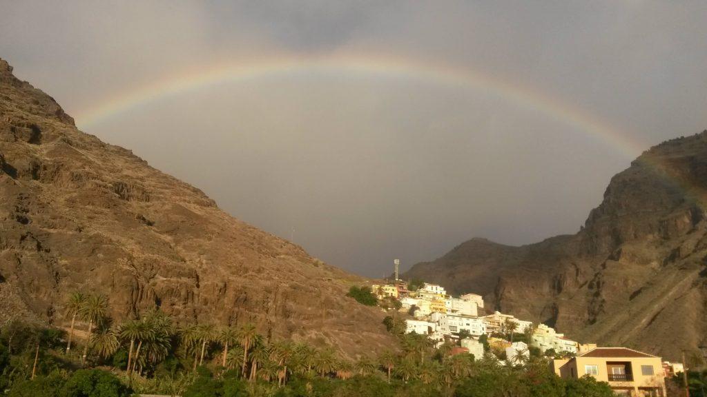 Regnbåge över en by som ligger vid foten av ett berg