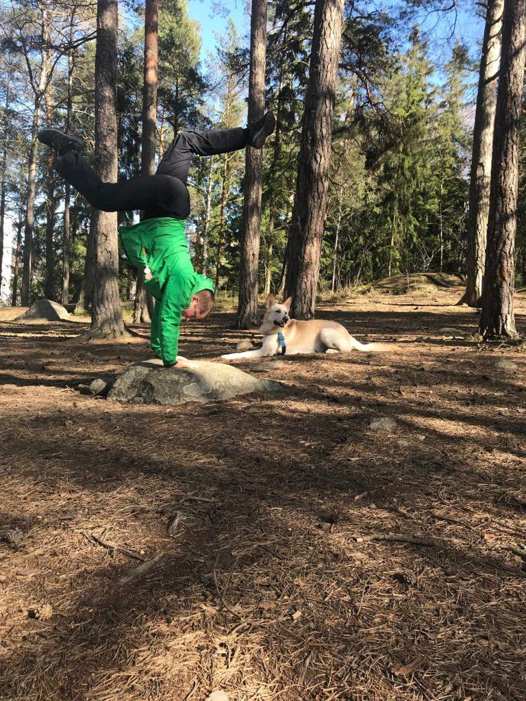 Jenny står på händer i skogen. Hunden Enzo ligger bredvid.