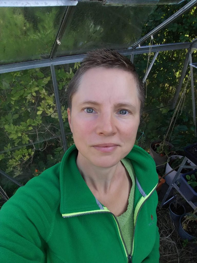 Jenny Forsberg i grön fleecetröja i ett växthus