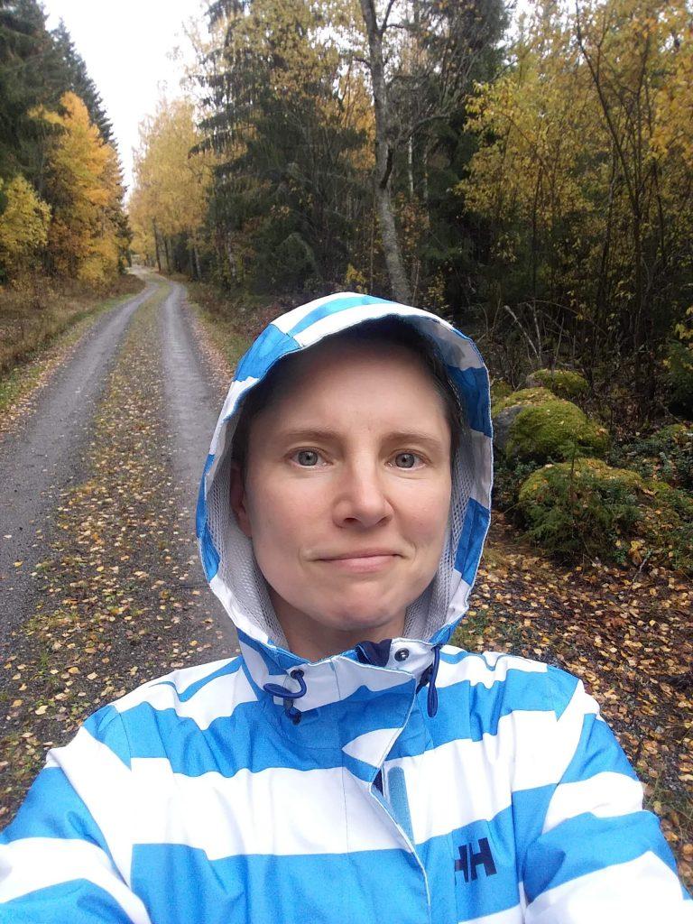 Jenny Forsberg i regnjacka på höstig skogsväg